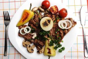 mooi geserveerd eten op plaat, vlees met ingrediënten van natuurlijke groenten foto