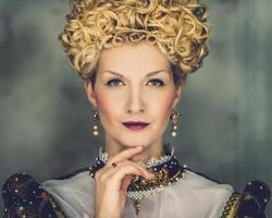 portret van mooie hooghartige koningin in koninklijke jurk foto