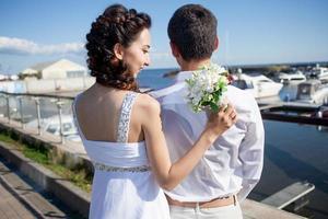 bruid en bruidegom op de achtergrond van de jachtclub, jong blij foto