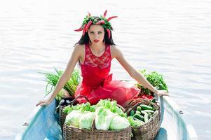 mooie vrouw met groenten in een boot foto