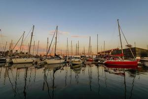 zee baai met jachten bij zonsondergang