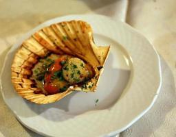 Sint-jakobsschelpgratin met citroen en peterselie in Italiaans zeevruchtenrestaurant foto