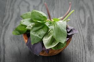 groene en paarse basilicum bladeren in houten kom op tafel foto