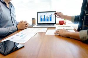professionals bespreken grafieken op laptop