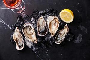 geopende oesters met ijs, citroen en wijn foto