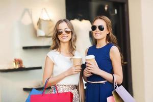 jonge vrouwen met boodschappentassen en koffie bij winkel foto