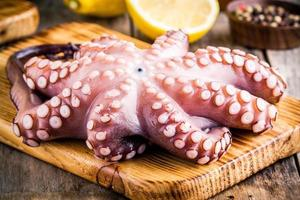 hele rauwe octopus op snijplank met citroen en peper