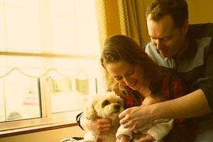 gelukkig jong gezin omarmt het eerste kind en de poedelhond foto