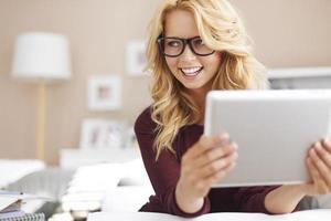 mooi jong meisje met behulp van digitale tablet thuis foto