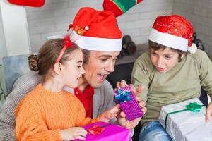 vader met twee kinderen openen kerstcadeautjes foto