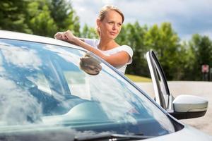 jonge, aantrekkelijke, gelukkige vrouw bij haar auto foto