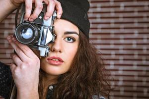 concept voor stijlvolle jonge vrouw in de buurt van bakstenen muur foto