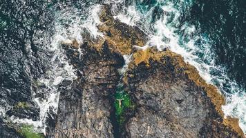een vrouw drijvend in een kleine rotsachtige vijver
