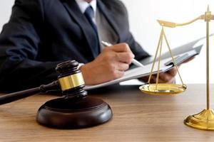 advocaat die aantekeningen maakt met hamer en schalen van rechtvaardigheid op bureau foto