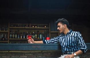 jonge man zit in een bar