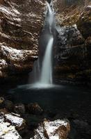 waterval op rotsachtige berg met sneeuw