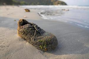 aangespoelde schoen aan kust foto