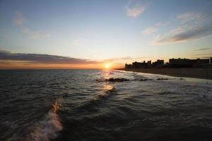 uitzicht op een stad aan de oceaan bij zonsondergang