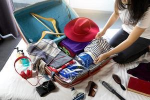 meisje inpakken van bagage haar reis voorbereiden foto