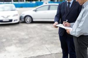 verzekeringsagent die een auto-ongeluk onderzoekt foto
