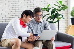Aziatische familie die creditcard gebruikt voor online transacties foto