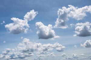 witte pluizige wolken in blauwe hemel op zonnig foto