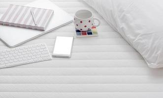 smartphonemodel met een laptop en koffie op een bed foto