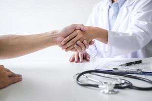 een close-up van een medische professional en een patiënt handen schudden