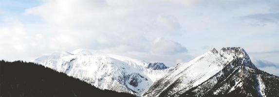 panoramisch uitzicht op een besneeuwde berg onder witte wolken