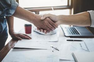twee mensen die elkaar de hand schudden in een kantoor