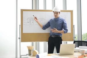 mannelijke ingenieur in harde hoed blauwdrukken bespreken foto