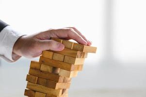 zakenman instortende gestapelde houten toren foto