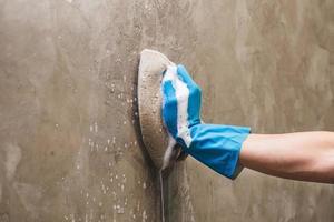 close-up van een persoon die een muur met een spons schoonmaakt foto