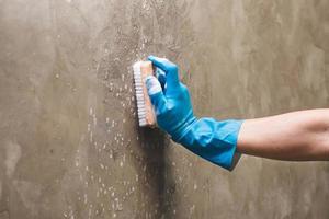 persoon die een muur schoonmaakt