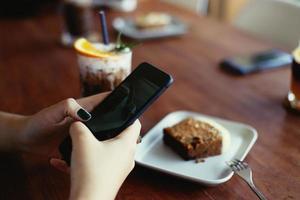 meisje gebruikt mobiele telefoon tijdens koffiepauze in café
