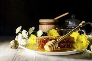 concept van honingraten en bloemen op witte houten achtergrond foto