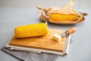 gekookte maïs en boter op snijplank. detailopname foto