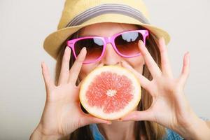 zomer. meisje toeristische grapefruit citrusvruchten te houden foto
