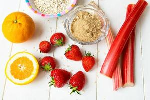 rabarber, aardbeien, bruine basterdsuiker, havermoutpap, sinaasappel foto