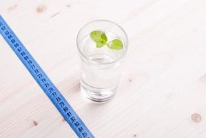 glas schoon water met munt op een tafel centimeter foto