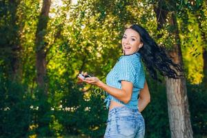 jonge hipster stijlvolle mooi meisje, luisteren naar muziek, mobiele telefoon foto