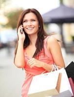 gelukkige vrouw met boodschappentassen en het gebruik van mobiele telefoon foto