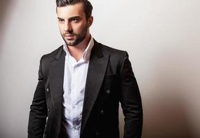 elegante jonge knappe man in zwart klassiek kostuum.