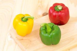groene zoete peper op houten plaat foto