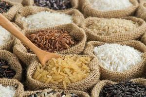 close-up bruine rijst met houten lepel in jutezak foto