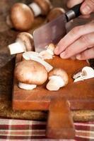 een champignons snijden op een houten bord foto