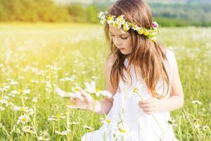 schattig kind meisje speelt met kamille bloemen foto
