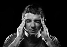 man met migraine en hoofdpijn ziek met handen op tempo foto