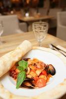 pasta met zeevruchten gekookt onder het blad van pizzadeeg foto