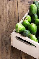 komkommers in een doos op een houten achtergrond.